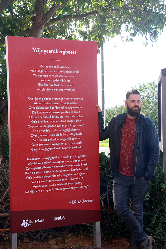 Dorpsdichter Jef Lemmens naast het paneel met zijn gedicht.